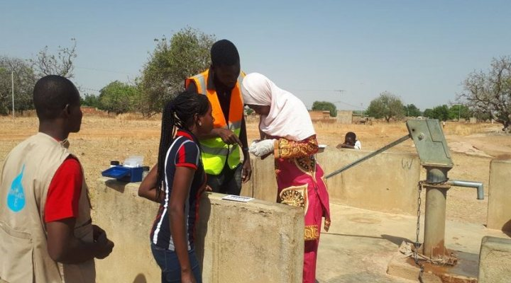 Woman collects drinking water at pump in Burkina Faso